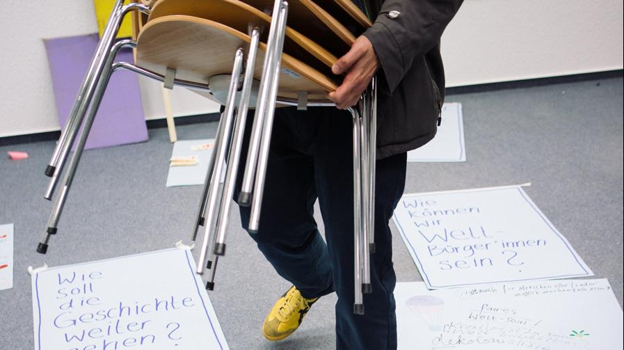 Eine Person schleppt gestapelte Stühle zwischen Collagen auf dem Boden