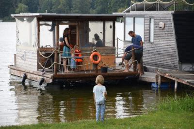 Ein kleiner Junge steht im Asa-FF Sommerlager 2018 am See und schaut auf ein überdachtes Boot, auf dem einige Menschen zu sehen sind